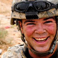 Specialist Olson, 3rd Platoon, 573rd Clearance Company, 1st Engineer Battalion, 130th Engineer Brigade, covered in dirt and concrete, takes time to smile for the camera after working for several hours in the high heat of Iraq.  Olson, along with his fellow engineers, was denying access to culverts that ran underneath main supply routes.  In the process, Olson broke an expensive pair of sunglasses; this photo is his reaction..This is a close up of SPC Olson's face.