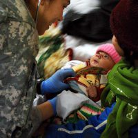 Avalance Baby - Private 1st Class Nichole Hill, medic with Task Force Workhorse, 3rd Combat Aviation Brigade, TF Falcon, checks the vitals on a Afghan baby, Feb. 9 at Bagram Airfield, Afghanistan. The baby was a victims of an avalanche that occurred the previous evening north of Bagram. (Photo by Army Spc. Monica K. Smith, 3rd Combat Aviation Brigade, TF FALCON, Public Affairs Office)