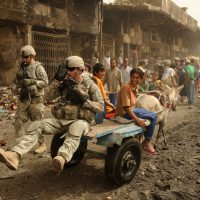 A U.S. Army Soldier from the Task Force Regulars 1st Brigade, 6th Infantry gets a lift from an Iraqi boy and his mule on route Douglas in the Jameela Market area on May 31, 2008.