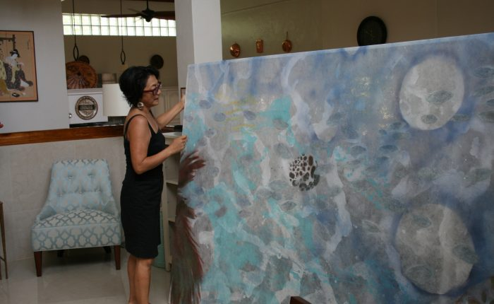 Artist Noe Tanigawa prepares to install her painting at the residence of U.S. Ambassador to Palau.